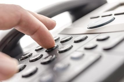 Telemarketer using a phone to dial a lead